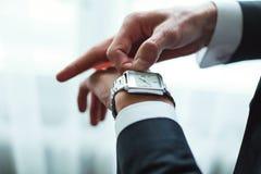 O homem de negócios ajusta o tempo em seu relógio de pulso Foto de Stock Royalty Free