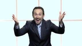 O homem de negócios alegre levantou as mãos no excitamento video estoque