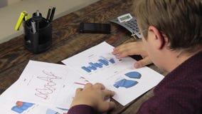 O homem de negócios analisa cartas e contagens em uma calculadora vídeos de arquivo