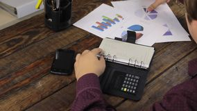 O homem de negócios analisa cartas e contagens em uma calculadora filme