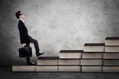 O homem de negócios anda na escada dos livros Fotografia de Stock