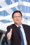 O homem de negócios ao ar livre prende para fora sua mão para agitar Imagens de Stock