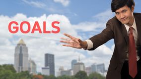 O homem de negócios apresenta objetivos de uma palavra com suas próprias mãos Fotografia de Stock