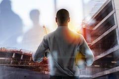 O homem de negócios Architect analisa os trabalhos de uma construção Exposição dobro imagem de stock royalty free