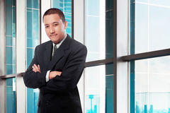 O homem de negócios asiático com braços cruzou a posição no escritório Imagens de Stock Royalty Free