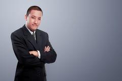 O homem de negócios asiático com braços cruzou a posição sobre o backgroun cinzento Foto de Stock