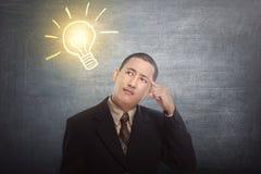 O homem de negócios asiático de pensamento obteve a ideia com a ampola brilhante sobre fotos de stock