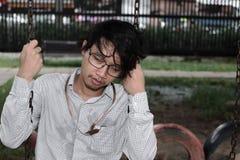 O homem de negócios asiático deprimido Tired senta-se no parque conceito do negócio do desemprego imagens de stock royalty free