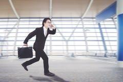 O homem de negócios asiático está correndo no salão da chegada fotografia de stock
