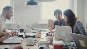 O homem de negócios asiático feliz toma um globo pequeno, pontos no país na reunião multi-étnico do escritório no sótão claro que filme