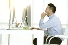 O homem de negócios asiático novo está sentando-se e bocejo no escritório moderno imagem de stock