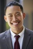 O homem de negócios asiático novo sorri à câmera, fim acima, vertical Imagem de Stock Royalty Free