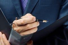 O homem de negócios assina acima o contrato Fotos de Stock Royalty Free