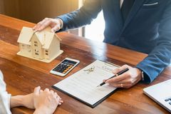 O homem de negócios assina o contrato atrás do modelo arquitetónico home Discussão com um staffalugado da empresa do mediador i fotos de stock royalty free