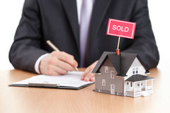 O homem de negócios assina o contrato atrás do modelo home Fotografia de Stock Royalty Free