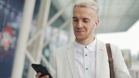 O homem de negócios atrativo novo anda abaixo da rua usando o telefone Escuta a música em fones de ouvido que anda em torno do filme