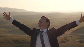 O homem de negócios aumenta as mãos e o sorriso video estoque