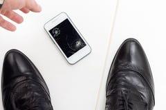 O homem de negócios aumenta seu smartphone quebrado Imagens de Stock Royalty Free