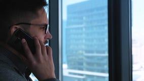 O homem de negócios bem sucedido novo com uma barba faz chamar um smartphone em um fundo da janela com uma vista da baixa filme