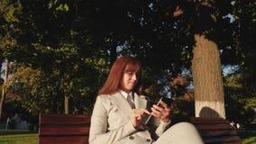 O homem de negócios bonito da mulher com vidros que datilografa um email na tabuleta no parque no banco iluminou-se pelo sol bril filme