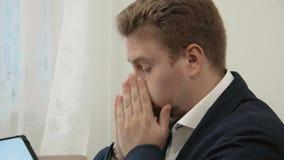 O homem de negócios cansado novo que trabalha em seu escritório na frente do laptop olha esgotado e gastado filme