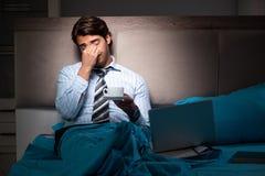 O homem de negócios cansado que trabalha fora do tempo estipulado em casa na noite fotos de stock