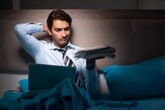 O homem de negócios cansado que trabalha fora do tempo estipulado em casa na noite fotografia de stock royalty free