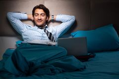 O homem de negócios cansado que trabalha fora do tempo estipulado em casa na noite foto de stock