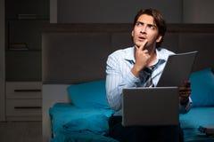 O homem de negócios cansado que trabalha fora do tempo estipulado em casa na noite imagens de stock