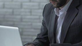 O homem de negócios cansado que trabalha no portátil, comerciante preocupou-se sobre a taxa de câmbio, close up video estoque