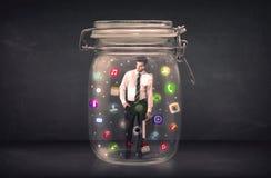O homem de negócios capturou em um frasco de vidro com o engodo colorido dos ícones do app Foto de Stock