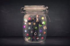 O homem de negócios capturou em um frasco de vidro com o engodo colorido dos ícones do app Imagens de Stock Royalty Free