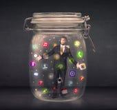 O homem de negócios capturou em um frasco de vidro com o engodo colorido dos ícones do app Fotografia de Stock Royalty Free