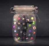 O homem de negócios capturou em um frasco de vidro com o engodo colorido dos ícones do app Imagens de Stock