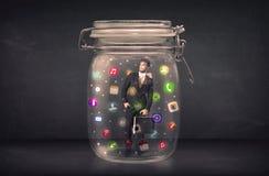 O homem de negócios capturou em um frasco de vidro com o engodo colorido dos ícones do app Fotografia de Stock