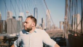 O homem de negócios caucasiano bem sucedido novo está de vista ao redor, sorrir feliz e cruza os braços na ponte de Brooklyn 4K vídeos de arquivo