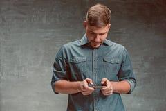 O homem de negócios caucasiano de sorriso dos jovens no fundo cinzento com telefone fotografia de stock royalty free