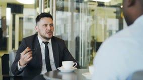 O homem de negócios caucasiano seguro no negócio do ajuste do vestuário formal encarrega-se a seu gerente afro-americano no café  video estoque