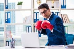 O homem de negócios com as luvas de encaixotamento irritadas no escritório fotos de stock