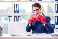 O homem de negócios com as luvas de encaixotamento irritadas no escritório foto de stock royalty free