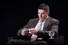 O homem de negócios com bebidas, os charutos e o dinheiro contam Imagem de Stock