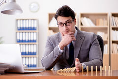 O homem de negócios com dominós no escritório imagens de stock