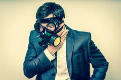 O homem de negócios com máscara de gás não pode respirar o ar mau fotografia de stock royalty free