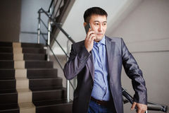 O homem de negócios com o telefone em sua mão fizer a chamada quando em escadas no prédio de escritórios durante a ruptura, vesti fotos de stock