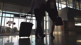 O homem de negócios com seu colega fêmea que anda entra completamente à mala de viagem do terminal e do rolo nas rodas Homem de n vídeos de arquivo