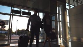 O homem de negócios com seu colega fêmea que anda entra completamente à mala de viagem do terminal e do rolo nas rodas Homem de n filme
