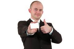 O homem de negócios com um cartão que levanta com polegares levanta o sinal Fotografia de Stock Royalty Free