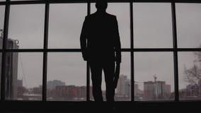 O homem de negócios com um caso vai à disposição à janela no escritório e aos olhares na cidade video estoque
