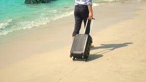 O homem de negócios com uma mala de viagem vai em um Sandy Beach branco conceito de freelancing, férias imagens de stock