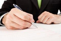 O homem de negócios completa um formulário. Foto de Stock